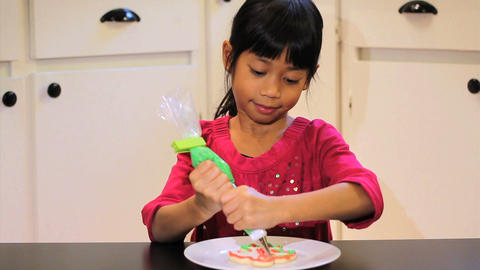 Proud Girl Finishes Decorating A Christmas Cookie Stock Video Footage