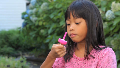 Smiling Asian Girl Finishes A Popsicle Stock Video Footage