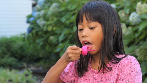Smiling Asian Girl Finishes A Popsicle stock footage