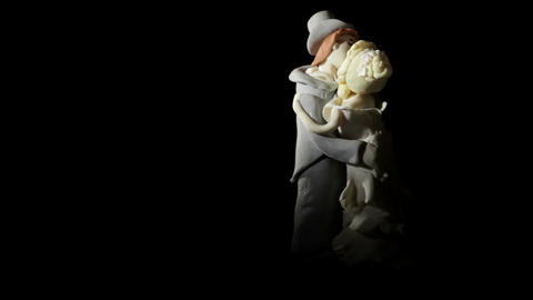 Wedding cake figurines rotating and kissing on black Stock Video Footage