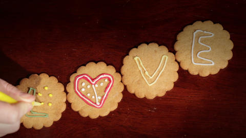 Drawing on ginger cookies. The word love Footage