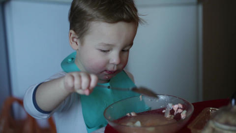 Two year old boy eats fish soup from the plate. Clip two Stock Video Footage