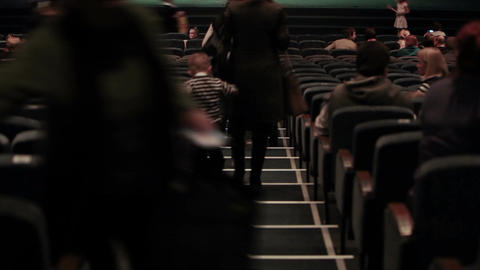 Audience fills the theatre. Defocused people shot from back. Time lapse Footage