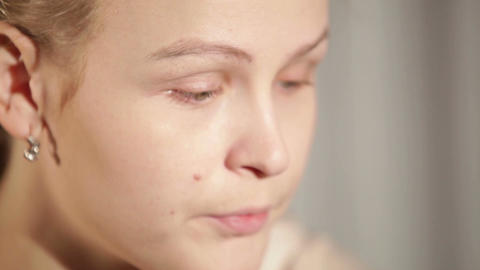Young woman is putting cosmetic cream on her face. Close up Stock Video Footage