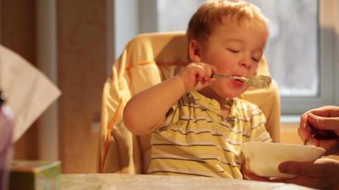 Little boy eats porridge Stock Video Footage