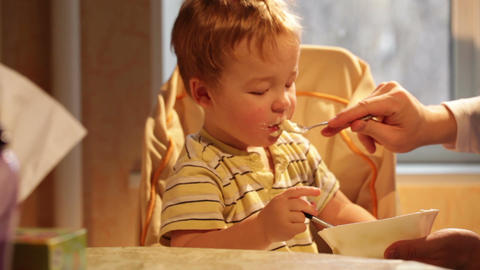 Little boy eats porridge Stock Video Footage