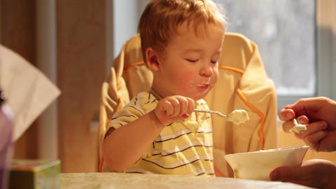 Little boy eats porridge Footage