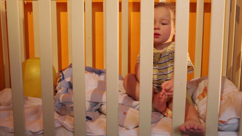 Kid sits in a playpen Stock Video Footage