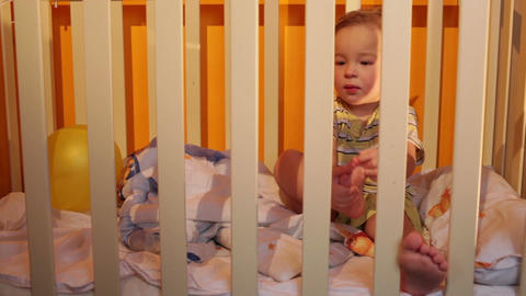 Kid Sits In A Playpen stock footage