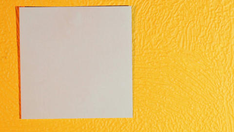 Hand sticks blank pink stick note on the yellow wall Live Action