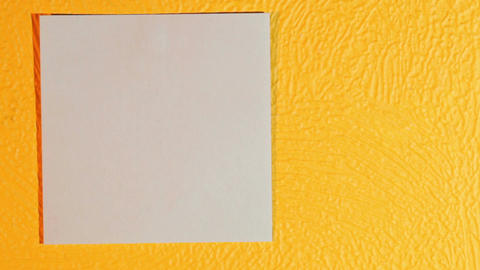 Hand sticks blank pink stick note on the yellow wall Stock Video Footage