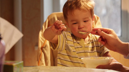 Little boy eats porridge. Time lapse Footage