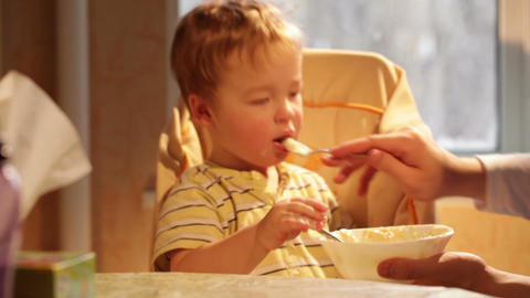 Little boy eats porridge. Time lapse Stock Video Footage