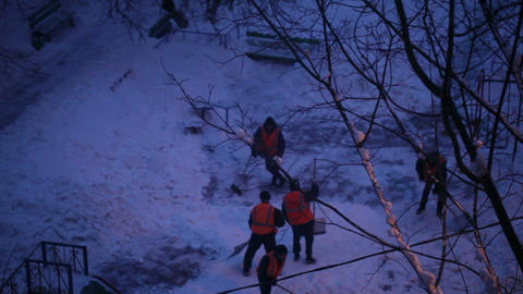 Street cleaners in orange uniform removing the snow. Real time Footage
