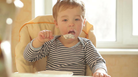 Little boy eats porridge in the morning Stock Video Footage