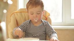 Little boy eats porridge in the morning Stock Video Footage