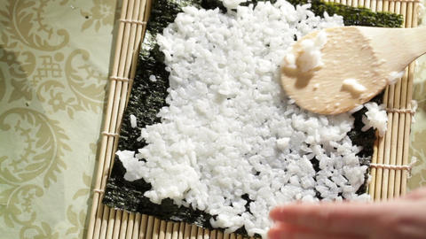 Putting rice on nori. Making sushi rolls. High angle view Stock Video Footage