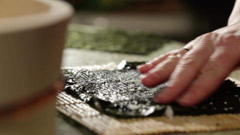 Putting wasabi on the nori while cooking sushi rolls Stock Video Footage