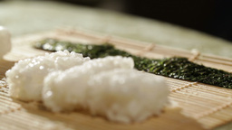 Putting wasabi on the nori while cooking sushi rolls Footage