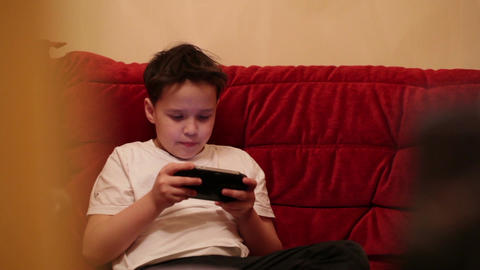 Teenager is playing his portable game console Stock Video Footage