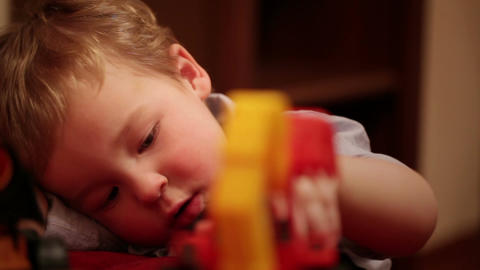 Two year old boy plays with toy trucks Stock Video Footage