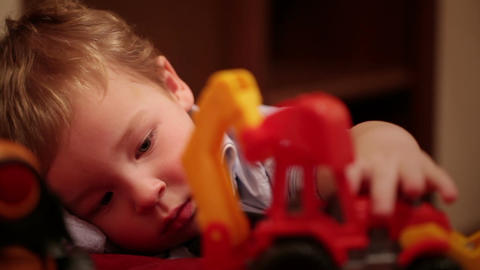 Two year old boy plays with toy trucks Footage