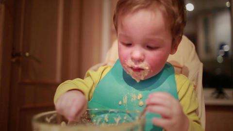 Two year old boy is having dinner independently Stock Video Footage