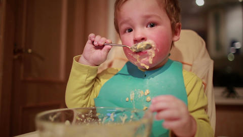 Two year old boy is having dinner independently Footage