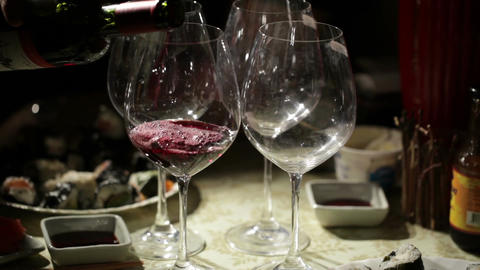 Red wine is poured in the glasses. Close up Footage