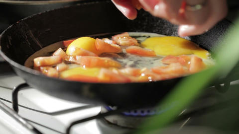 Egg frying in a pan. Adding tomato slices Stock Video Footage
