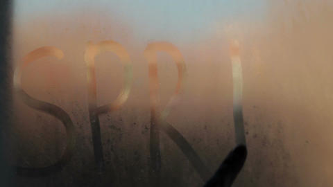 She writes the word spring on the steamy glass Stock Video Footage