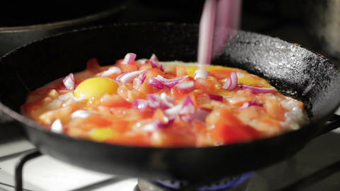 Egg frying in a pan. Adding onion slices Stock Video Footage