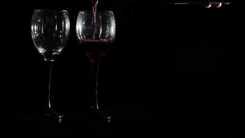 Red wine is poured into two glasses on black background Stock Video Footage