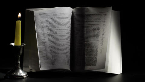 Candle, wind and Bible Stock Video Footage