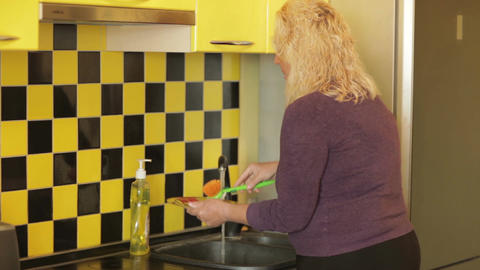 Middle-aged woman washing a plate in the yellow kitchen Stock Video Footage