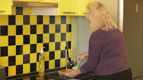 Middle-aged Woman Washing A Plate In The Yellow Kitchen. stock footage