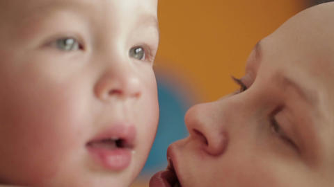 Happy cheerful family. Mother and baby kissing, laughing and hugging. Close ups Footage