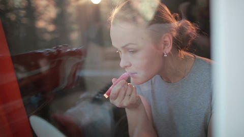 Through the window portrait of girl making her lips shine Stock Video Footage