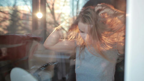 Through the window warm portrait of girl enjoying her hair. Beautiful back light Footage