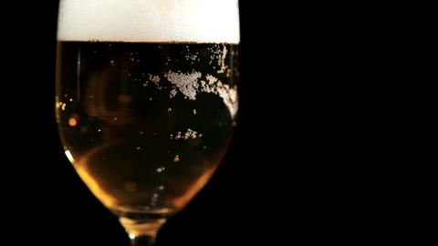 Glass of bear on black. Macro shot with foam and bubbles Stock Video Footage
