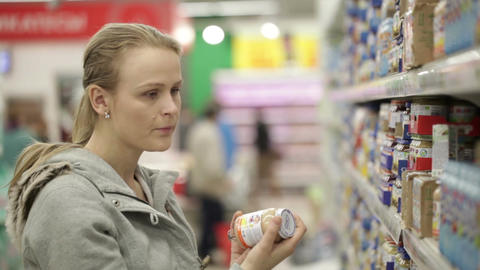 Young woman is choosing food for her child in the... Stock Video Footage