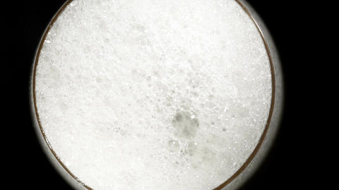 Beer pours in glass on black. High angle macro shot Stock Video Footage