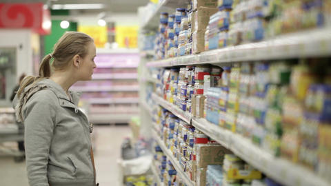 Young woman is choosing food for her child in the shopping center Footage