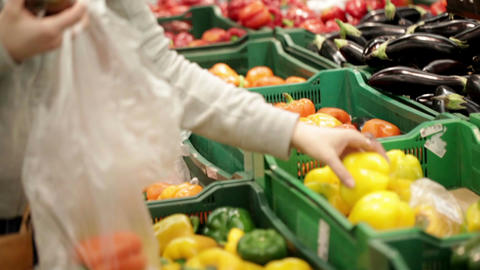 Woman in a supermarket choosing vegetables at the... Stock Video Footage