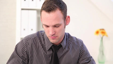Handsome young businessman sitting writing notes at his desk Stock Video Footage