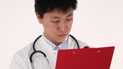 Close Up Of A Young Asian Doctor Writing On His Clipboard stock footage