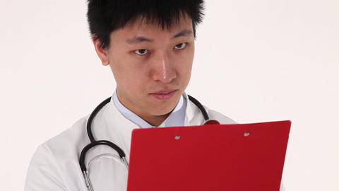 Close up of a young asian doctor writing on his clipboard Stock Video Footage