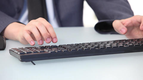 Asian man typing on a desktop keyboard, closeup of hands Footage
