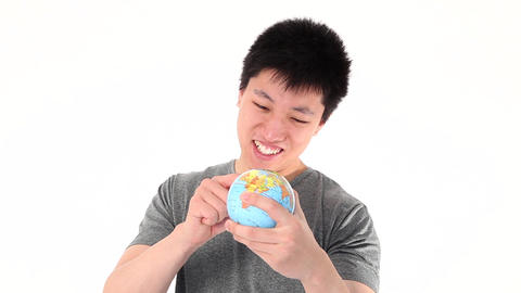 Funny Asian man pointing on a world globe Stock Video Footage