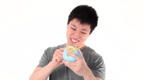 Funny Asian man pointing on a world globe Footage